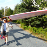 "Grady Watts jauntily shoulders ""Back to the Future"" strolling to Long Pond.  This 26' racing single has 12"" beam and weighs all of 30 pounds.   His ""rear view"" bicycle mirror allows a forward look while rowing."